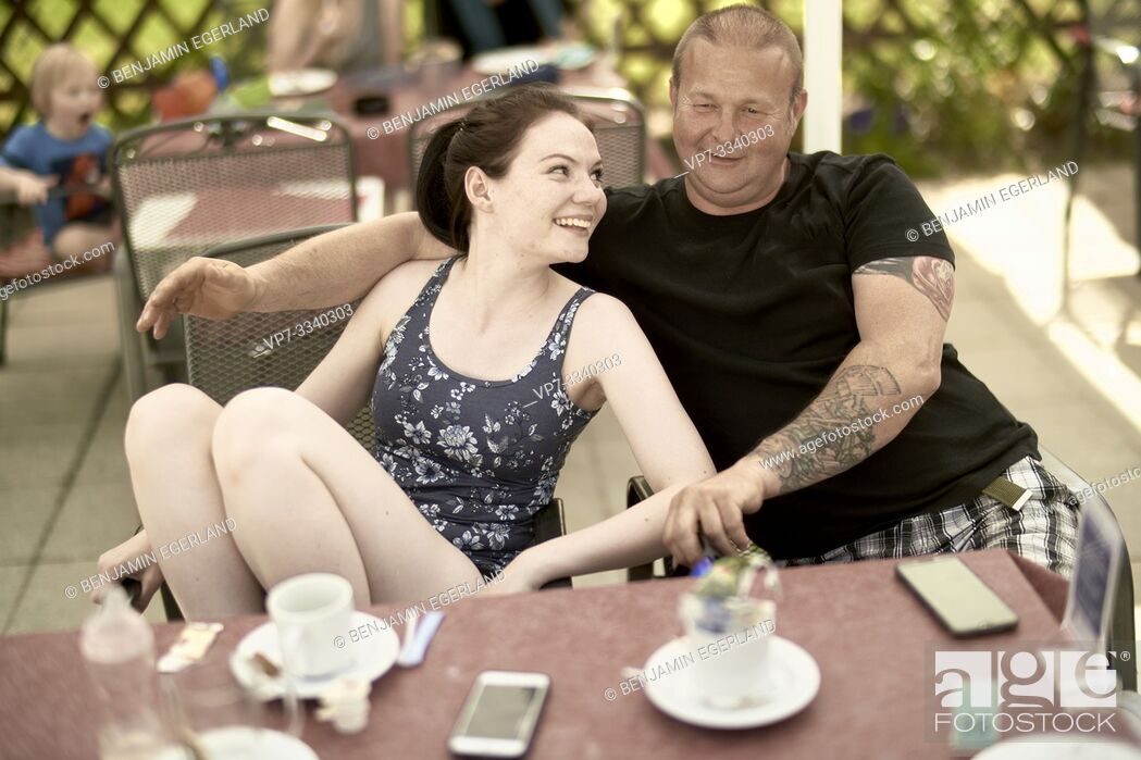Stock Photo: middle-aged father with young adult daughter sitting together at table in outdoor café.