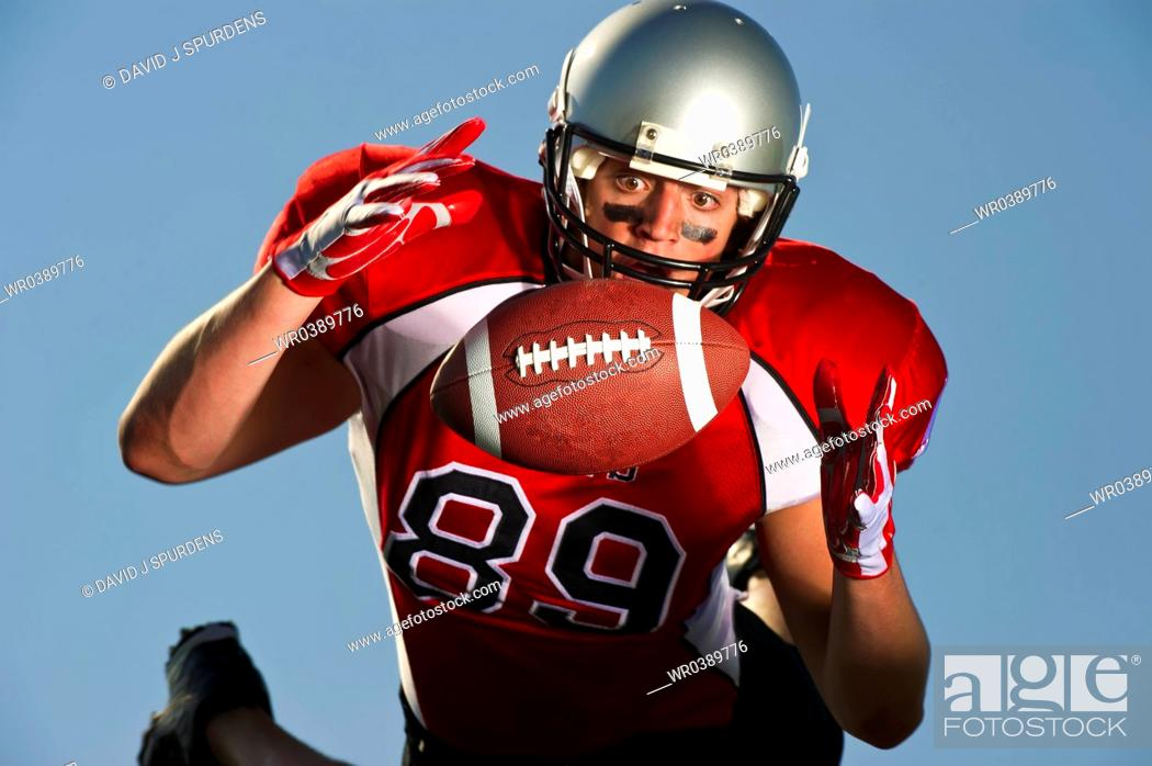 Stock Photo: American Football player focused on making the catch.