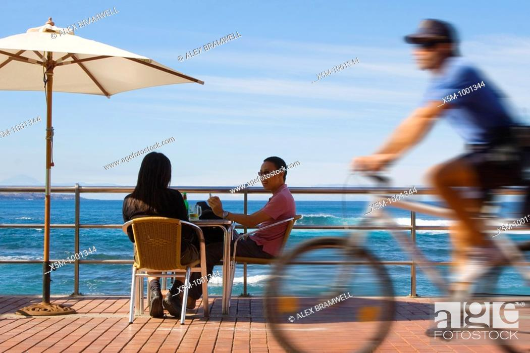Stock Photo: A couple sit at a beachfront table on Las Canteras Beachfront as a policeman cycles past.