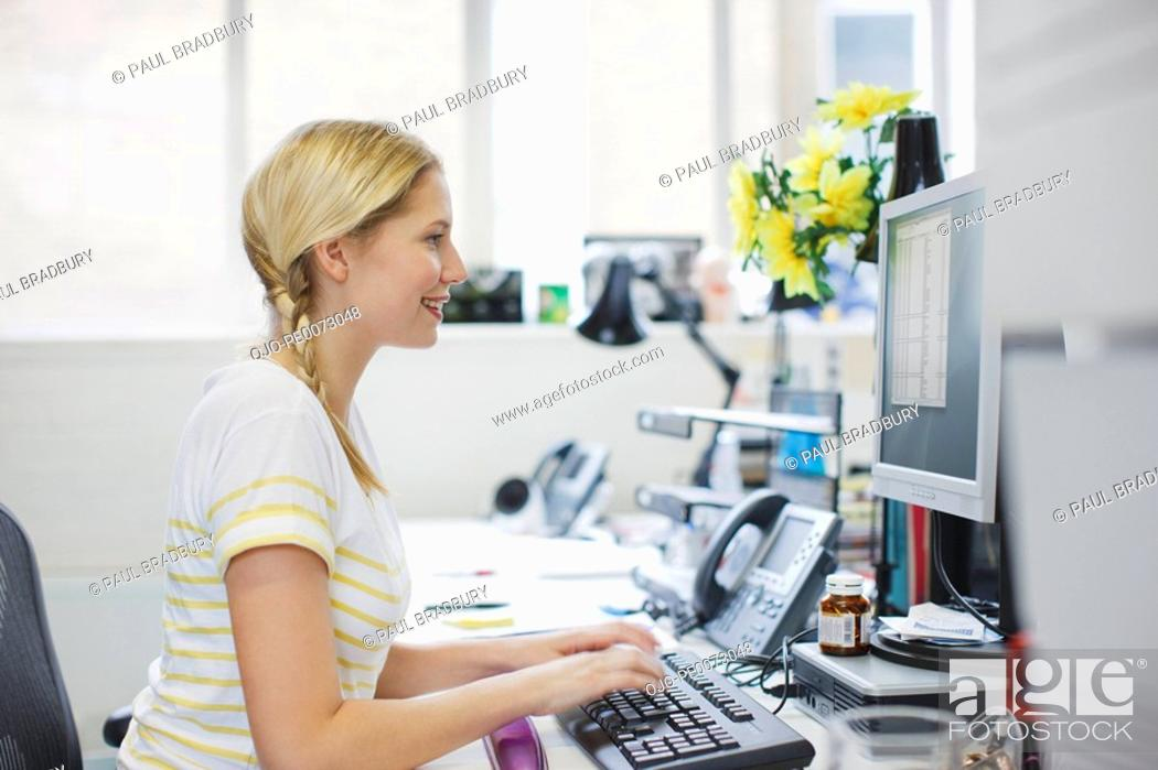 Stock Photo: Smiling businesswoman working at computer in office.