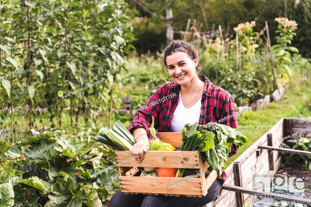 Imagen: Smiling young woman with vegetables in crate sitting against plants at garden.