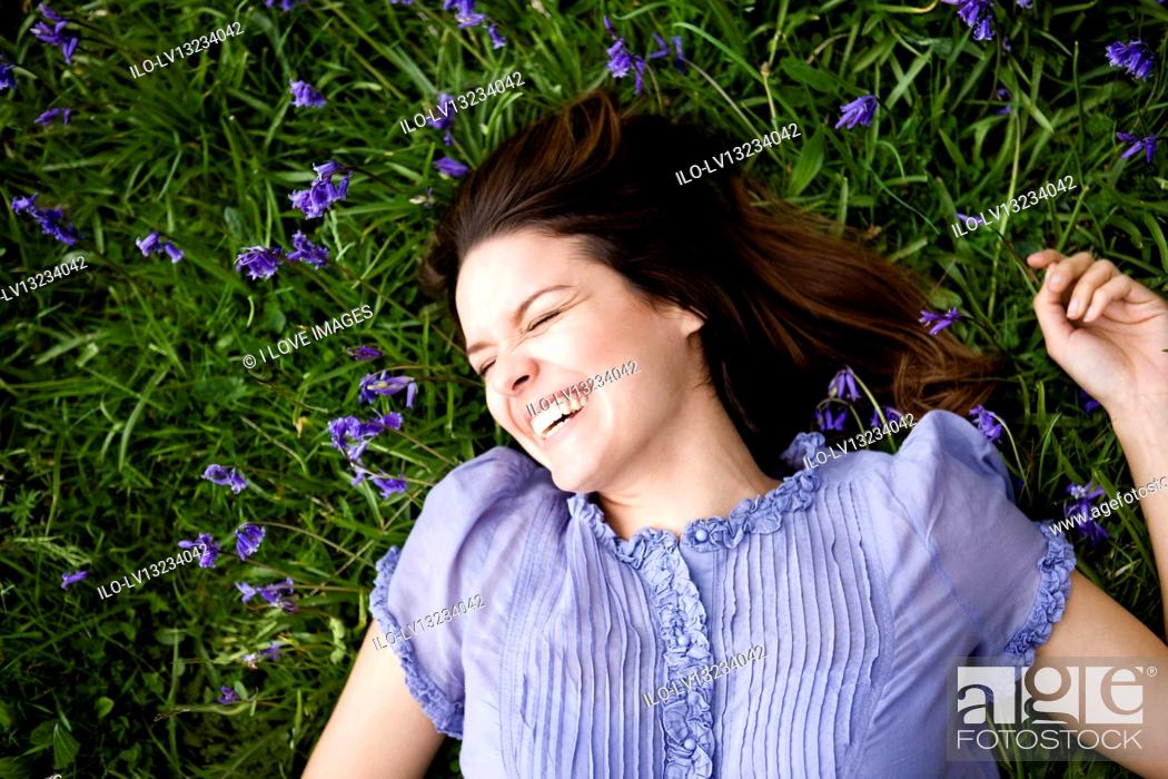 Stock Photo: A young woman lying amongst bluebells, laughing.