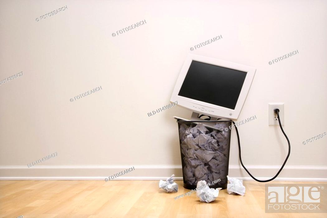 Stock Photo: Computer monitor in trash can surrounded by crumpled up paper.
