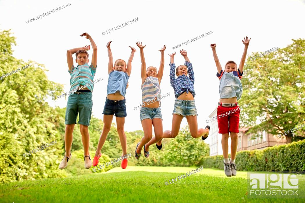 Stock Photo: friendship, childhood, leisure and people concept - group of happy kids or friends jumping up and having fun in summer park.