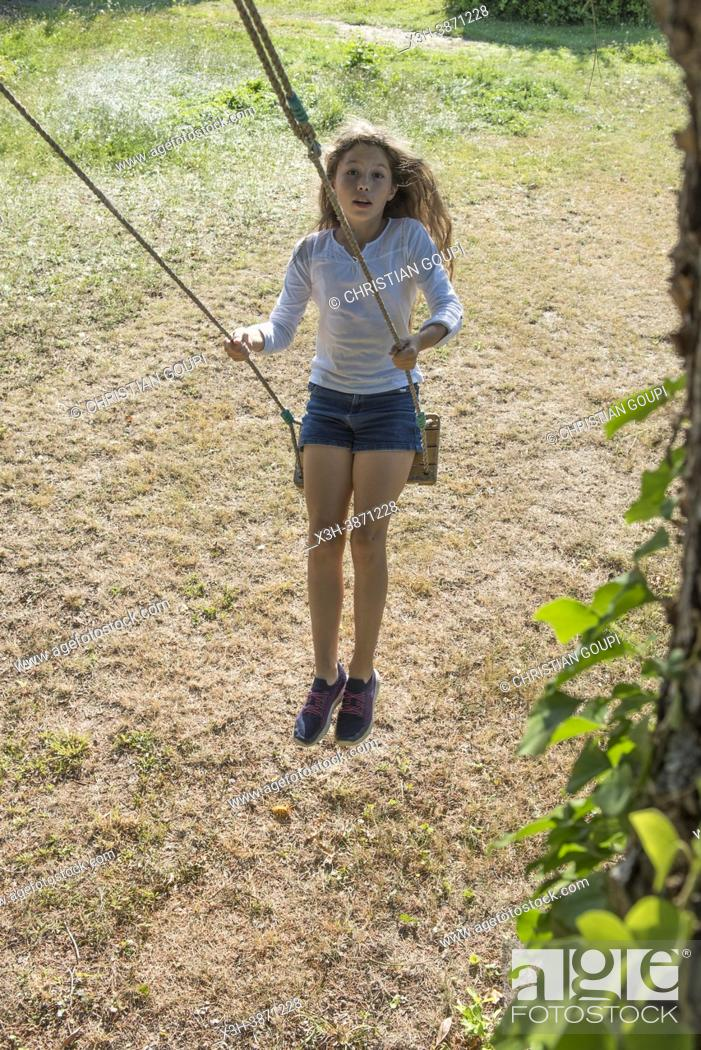 Photo de stock: Young girl in jeans shorts and white tunic on a swing in motion, France.