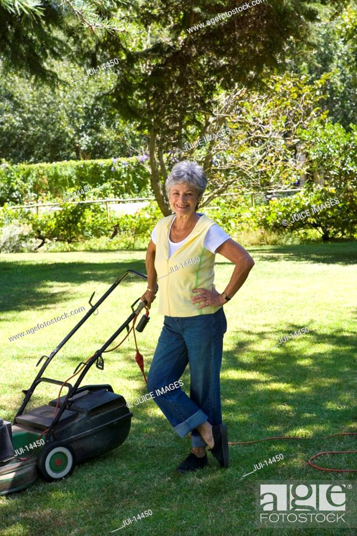 Stock Photo: Senior woman with lawnmower, hand on hip, smiling, portrait.