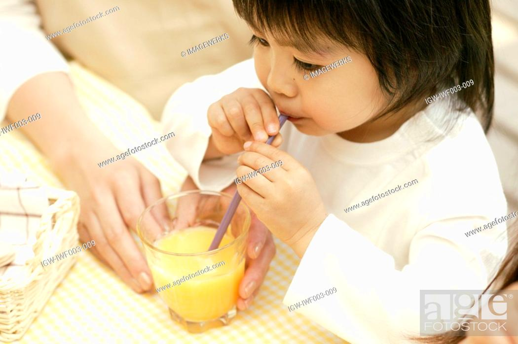Stock Photo: A small boy drinking juice with the help of a straw.