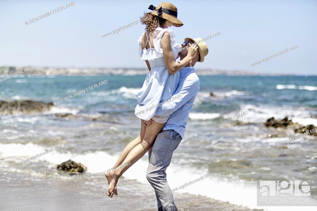 Stock Photo: man carrying woman at beach, love, couple, dating, honeymoon, in Hersonissos, Crete, Greece.