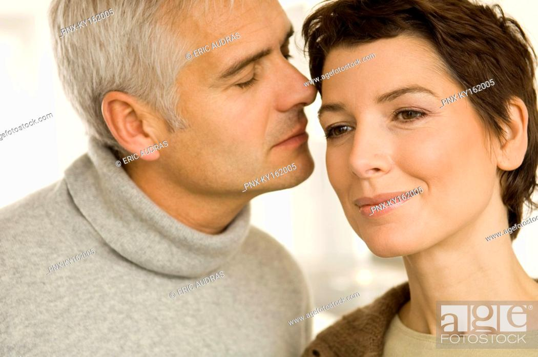 Stock Photo: Close-up of a mature man and a mid adult woman romancing.