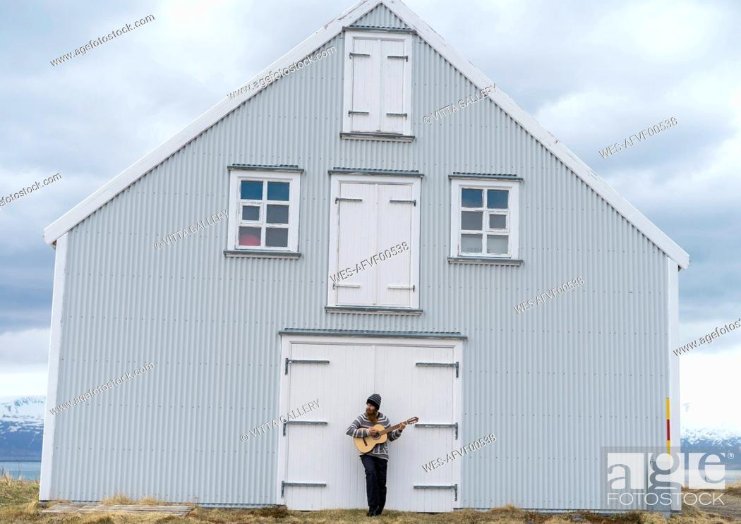 Stock Photo: Iceland, young man playing guitar, wooden house.