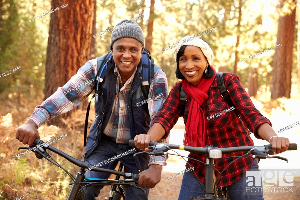 Stock Photo: Portrait Of Senior Couple Cycling In Fall Woodland.