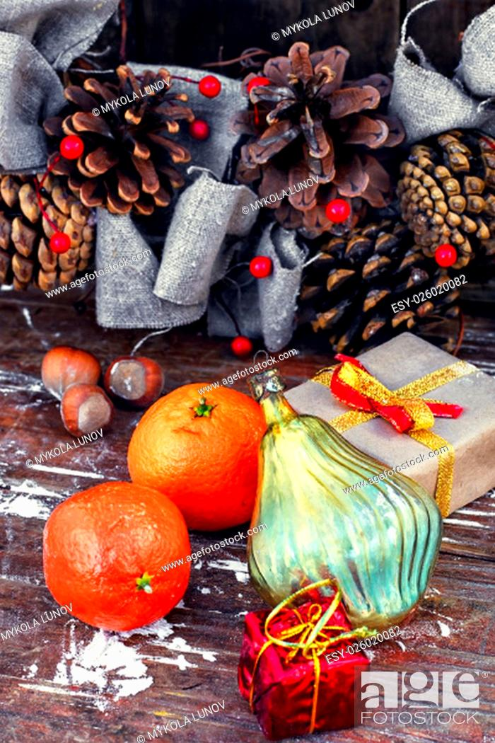 Stock Photo: Winter composition with tangerines,pine cones and gifts.