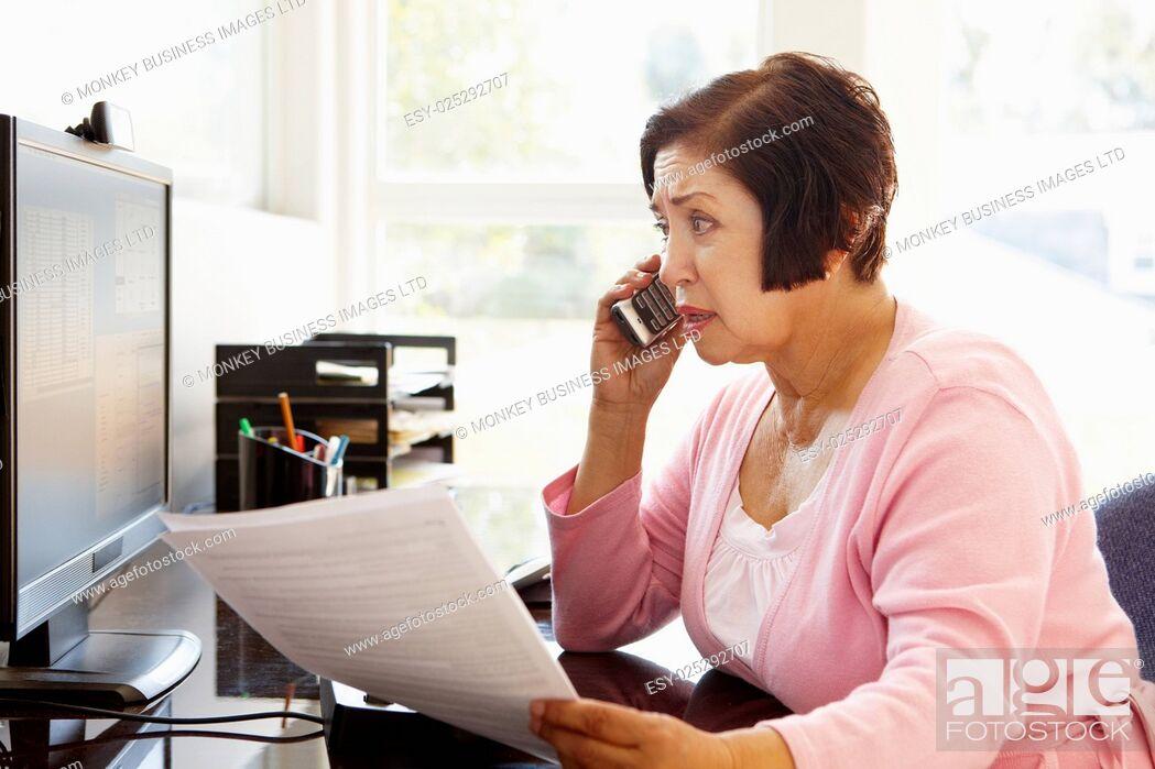 Stock Photo: Senior Hispanic woman working on computer at home.