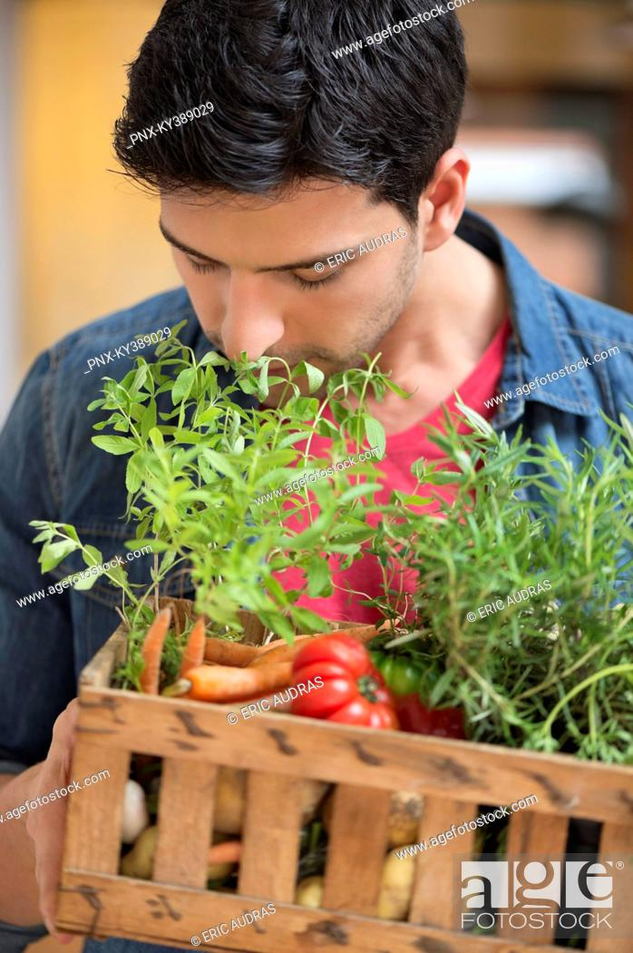 Stock Photo: Man carrying fresh vegetables in a crate.