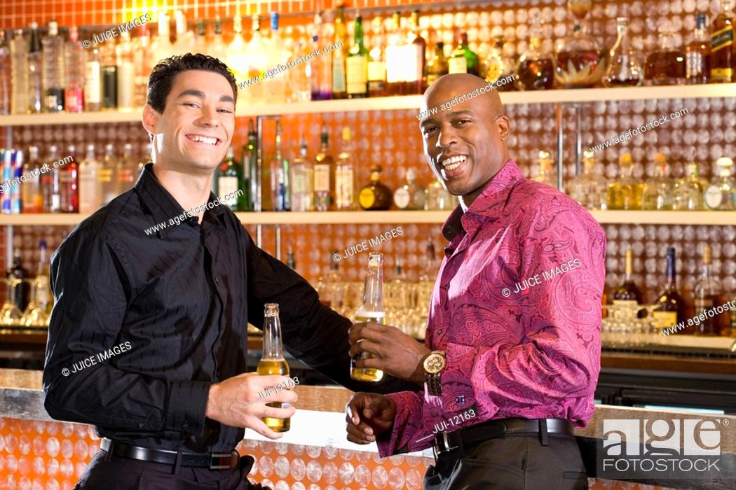 Stock Photo: Young man and friend at bar with drinks, smiling, portrait.