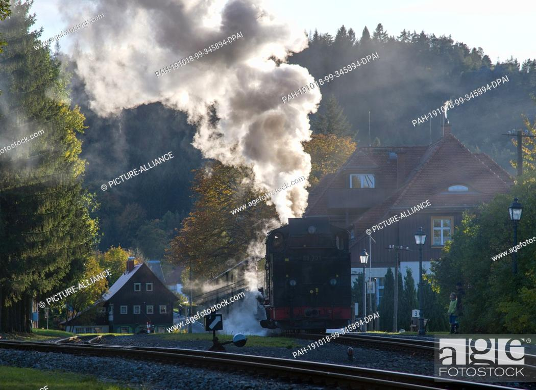Stock Photo: 10 October 2019, Saxony, Jonsdorf: A steam locomotive of the Zittau narrow-gauge railway stands at the station of the Kuort.