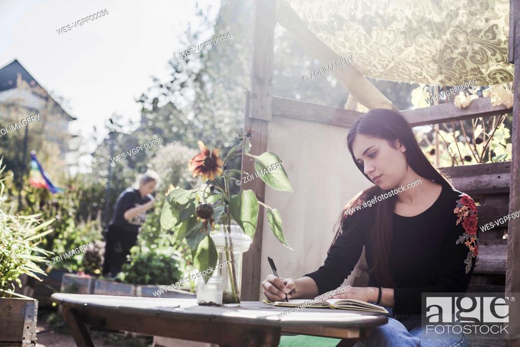 Stock Photo: Young woman relaxing in urban garden.