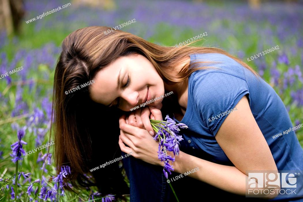 Stock Photo: A young woman holding a bunch of bluebells.