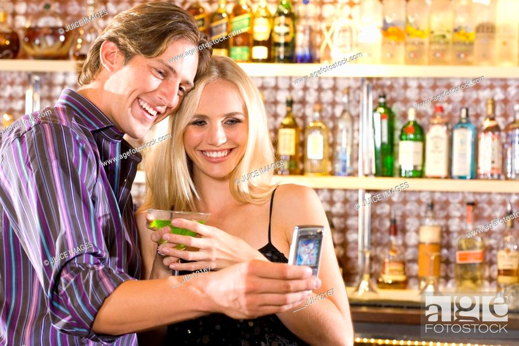 Stock Photo: Young couple at bar with drinks, taking photograph of themselves, smiling.