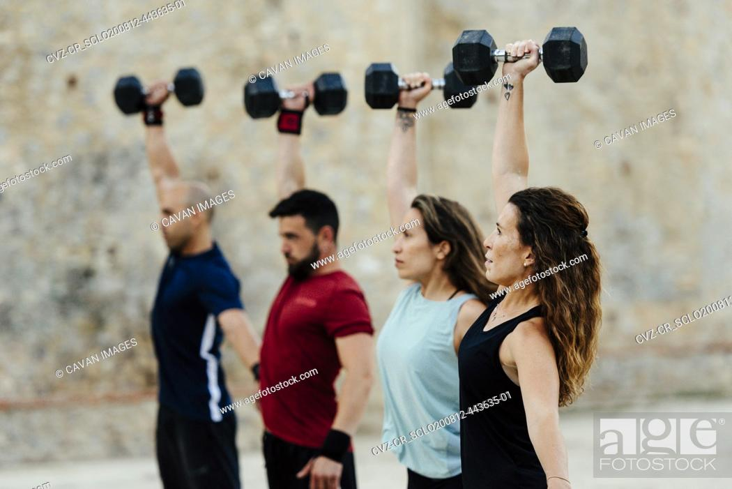 Stock Photo: Athletes lifting a crossfit weights in an urban enviroment.