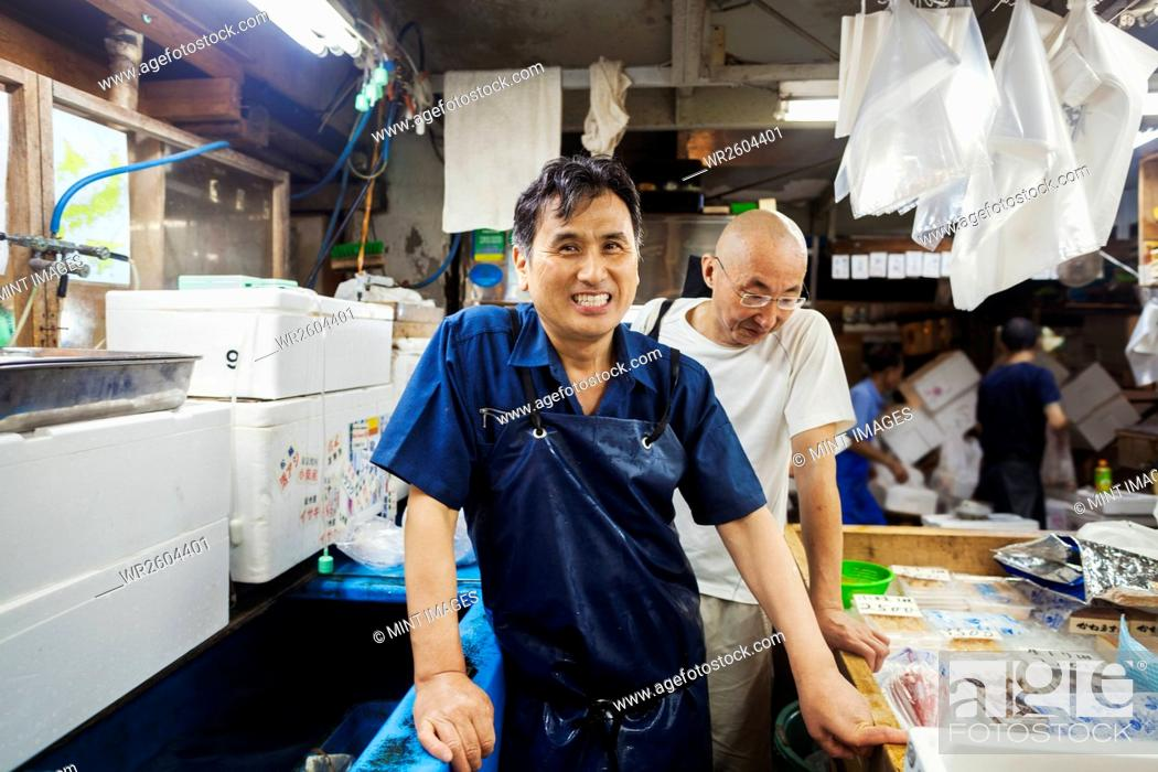 Stock Photo: A traditional fresh fish market in Tokyo. Two men in aprons working on a fresh produce stall.