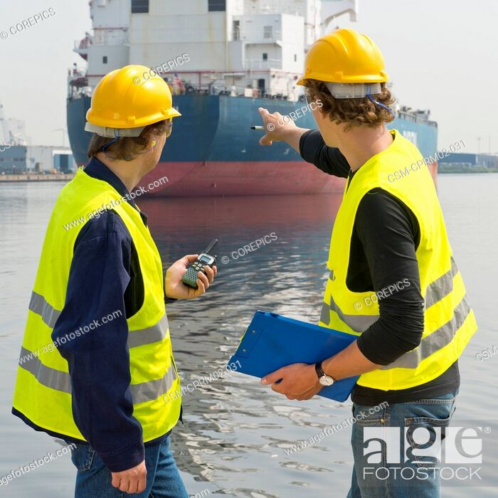Stock Photo: Two dockers talking about a large oil tanker, one with a cb radio, and the other pointing at the industrial vessel with a clip board in his hand.