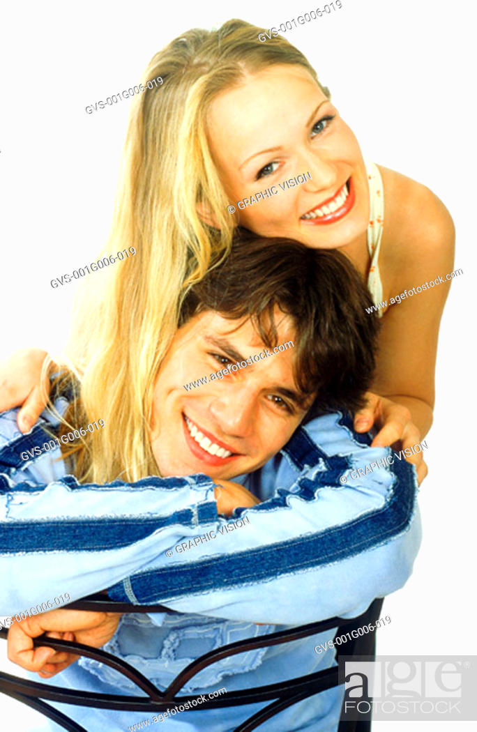 Stock Photo: Portrait of a young man sitting on a chair with a young woman standing behind holding him.