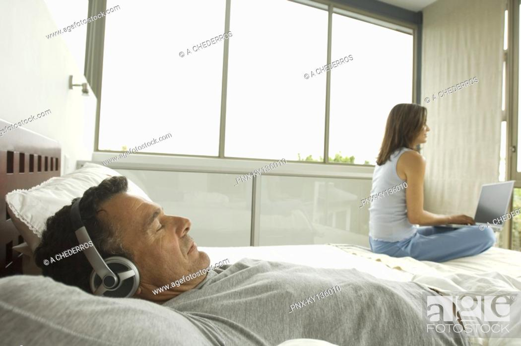 Stock Photo: Couple in bedroom, man listening to music, woman using laptop, indoors.