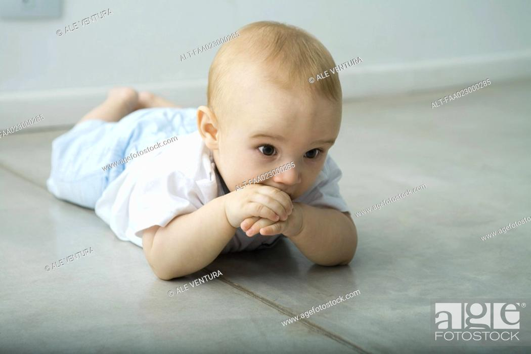 Stock Photo: Baby lying on floor, hand in mouth.