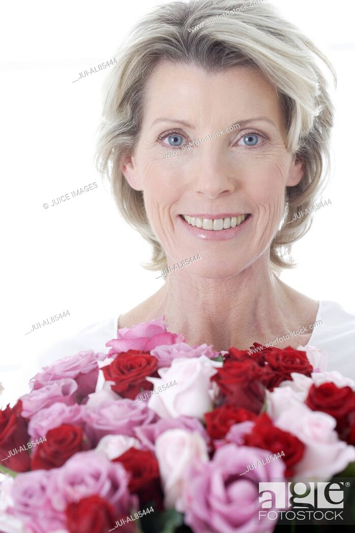 Stock Photo: Senior woman smiling and holding bouquet of flowers.