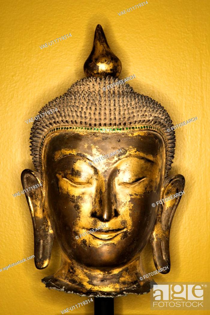 Stock Photo: Bronze Buddha head from Thailand against yellow wall.