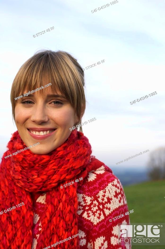 Stock Photo: Young woman with scarf and cardigan under the sky, close-up.