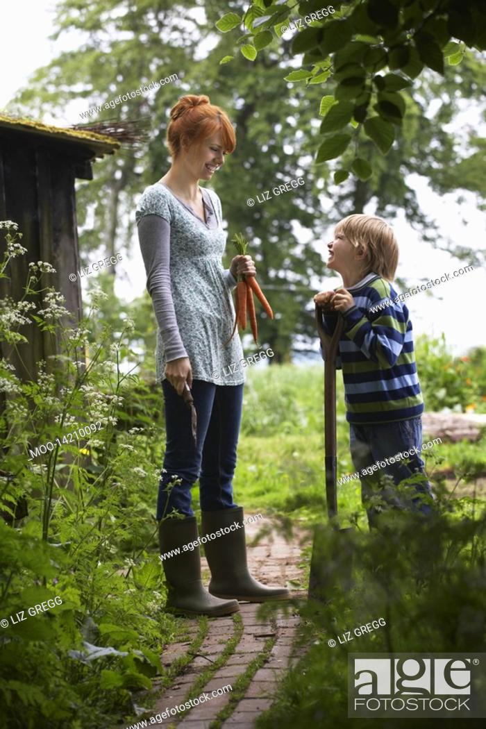 Stock Photo: Mother and son 5-6 with spade in countryside.