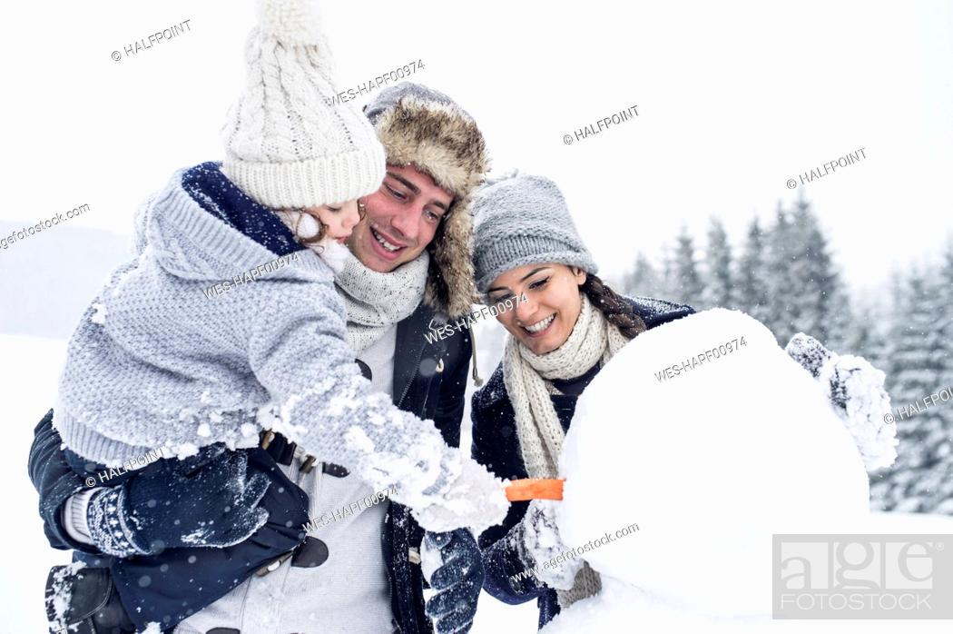 Stock Photo: Family building snowman together.