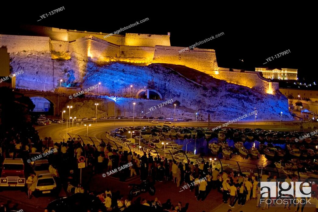 Stock Photo: Crowd lining the streets surrounding Fort Saint-Nicholas illuminated at night with view of Pharo Palace in the distance, Marseille, France.