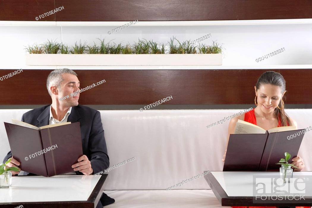 Stock Photo: Woman and man with menus flirting.