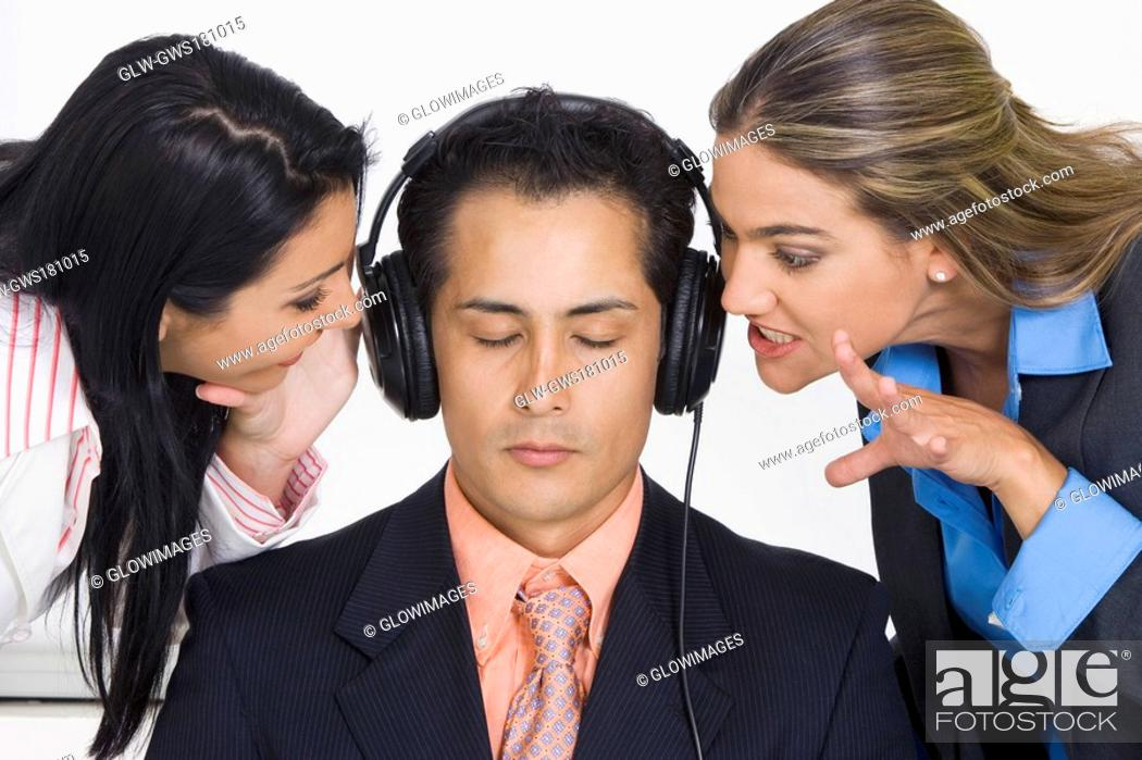Stock Photo: Close-up of a businessman listening to music while two businesswomen bothering him.