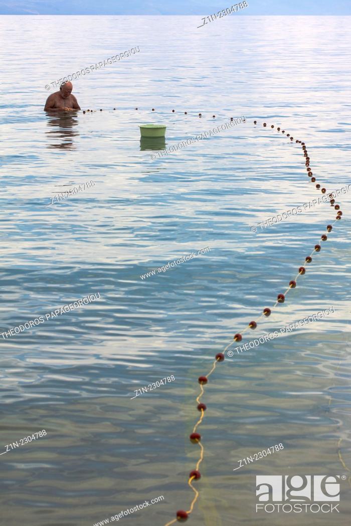 Stock Photo: A fisherman at Peroulia beach. Messenia, Peloponnese, Greece.