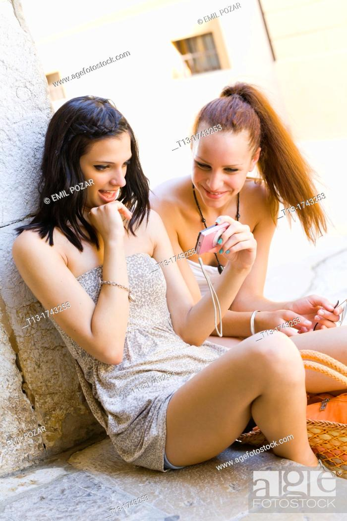 Stock Photo: Two girfriends are reviewing digital pictures on a photo camera.