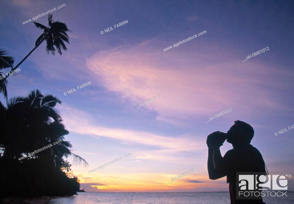 Stock Photo: Man blowing inro a seashell, Samoa.