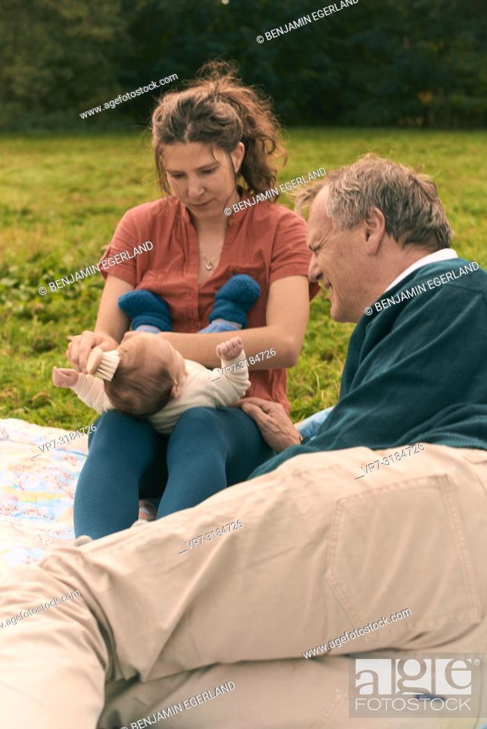 Imagen: couple, baby, family, age difference, outdoors, in park, generations, Grandfather, at Neuhofener Berg, Munich, Germany.