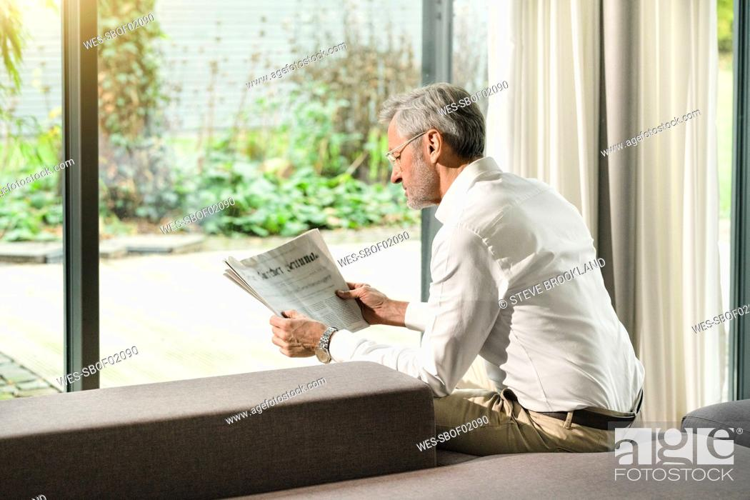 Stock Photo: Senior man with grey hair in modern design living room reading newspaper.