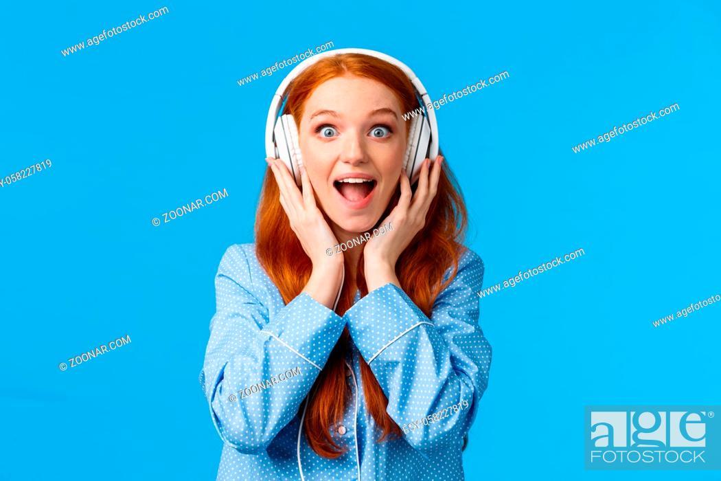 Stock Photo: Excited and amused attractive caucasian redhead woman in pyjama, screaming from fascination and amazement hear new song, wearing headphones enjoy music.