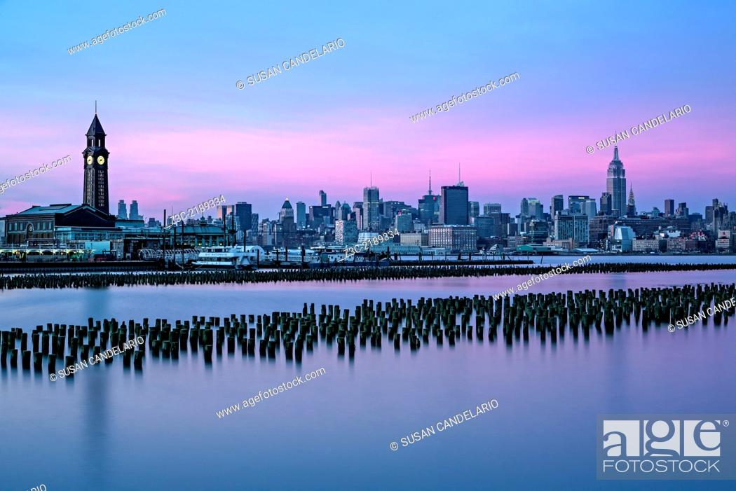 Stock Photo: The New York City skyline along with Empire State Building illuminated in pastel colors and the Erie Lackawanna Terminal in Hoboken.
