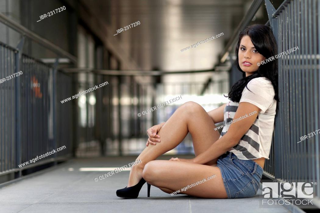 5141d72c4b22 Stock Photo - Young woman in a stripy T-shirt and denim hot pants and black  high heels