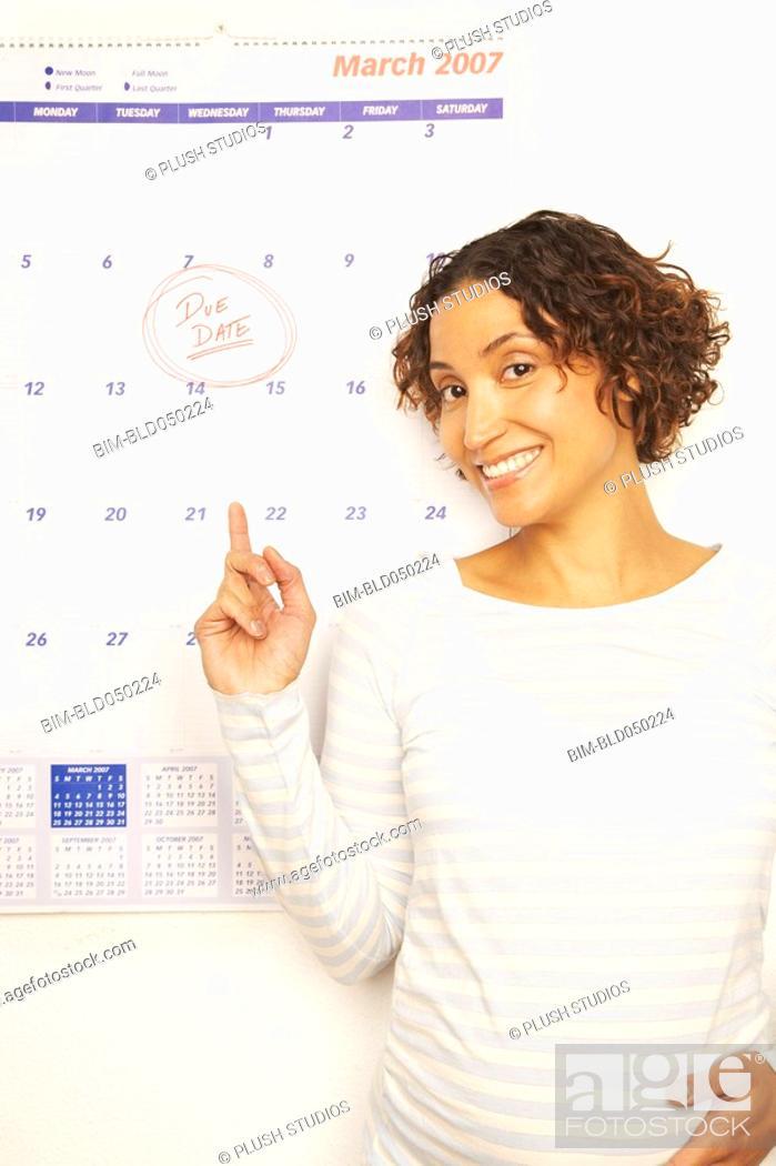 Stock Photo: Pregnant Mixed Race woman next to calendar.