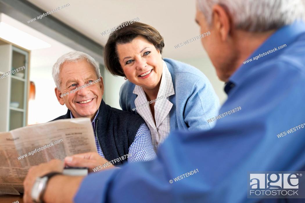 Stock Photo: Germany, Leipzig, Senior man reading newspaper, man and woman smiling.