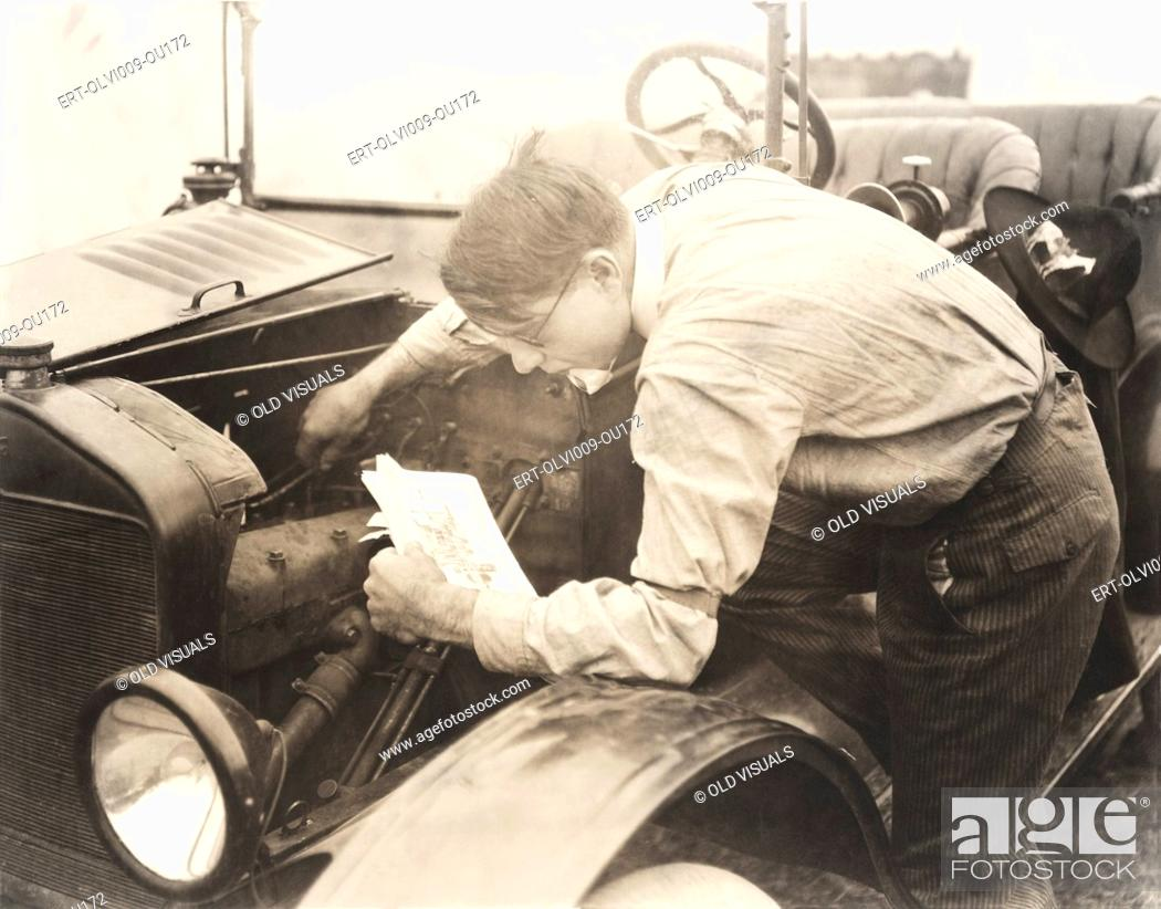 Stock Photo: Man reading instructions on how to fix car.