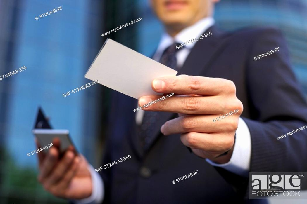 Stock Photo: Man holding a calling card into the camera.