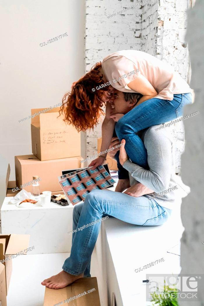 Stock Photo: Romantic couple moving into industrial style apartment, woman sitting on boyfriend's shoulders holding photographs.